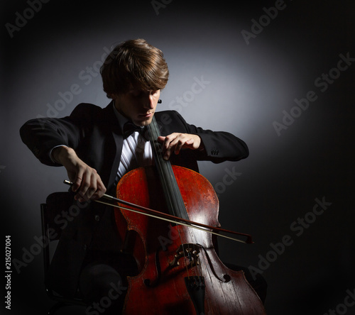 Foto Spatwand Muziek Young man playing the cello. Portrait of the cellist on a dark background.