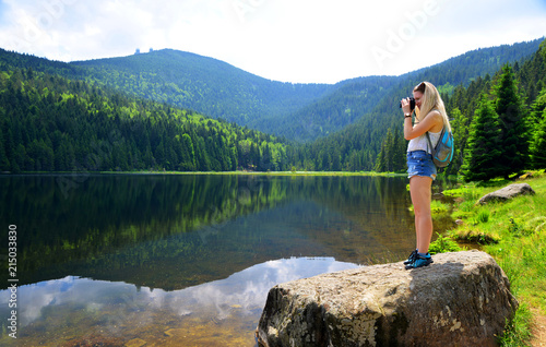 Leinwandbild Motiv Nature photographer taking picture photos with DSLR camera moraine lake Kleiner Arbersee in National park Bavarian forest. Germany.