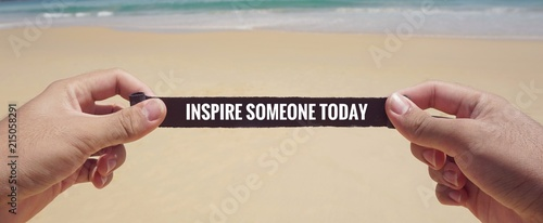 Motivational and inspirational quote - 'Inspire someone today' written on a piece of paper. With vintage styled background.