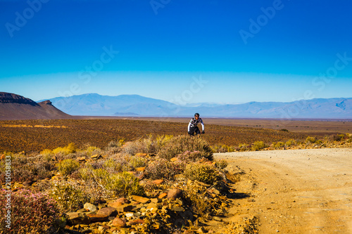 Canvas Honing A man rides his bicycle on a dirt road in the mountains of the Karoo, South Africa