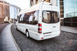White mini bus moves down the street - 215077052