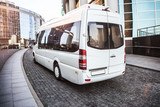 Fototapeta Miasto - White mini bus moves down the street © Yuri Bizgaimer