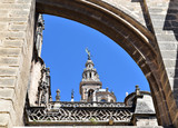 Flying buttress, Gothic style architectural detail of Seville Cathedral in Spain and Giralda Tower at background