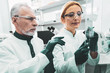 Test tubes. Two busy chemists feeling responsible while holding test tubes in hands sitting in laboratory