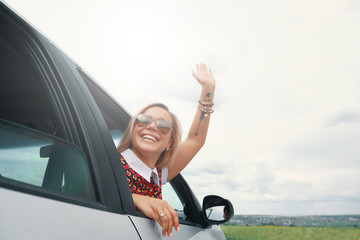 Young woman enjoying the road trip by car