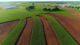 Strip farming fields, agricultural landscape in the early morning.
