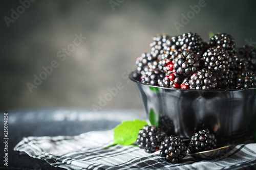 Ripe blackberry on a wooden table. Dark background. - 215094050