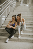 Two female runners looking on smart phone an rest after jogging - 215102240