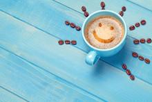 """Постер, картина, фотообои """"Kaffee Tasse mit lächelndem Gesicht Emoji Smiley auf blauem Holz Tisch"""""""