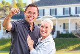 Young Adult Couple With House Keys In Front of Beautiful Home - 215111653