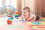 Portrait of cute adorable blond Caucasian smiling child boy with blue eyes crawling on floor in kids children room. Little baby playing with toys on playmat at home. Early education development - 215111839