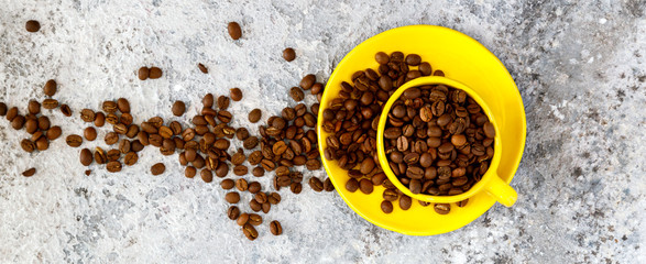 Coffee Beans Fragrant in the Yellow Cup on the Gray Background. Top View. Copy space for Text.Banner © lily_rocha