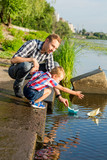 Dad helps the Little Boy to lower the paper boat to the water. Dad and a little son launch paper boats in a river in the summer - 215144016