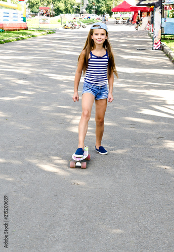 Foto Spatwand Skateboard Adorable happy smiling little girl child with skateboard outdoors
