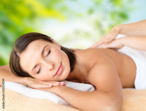 wellness, spa and beauty concept - close up of beautiful woman having massage over green natural background © Syda Productions