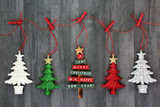 Hanging Christmas tree bauble decorations on a string line with pegs on rustic wood background. Festive Christmas card for the holiday season.