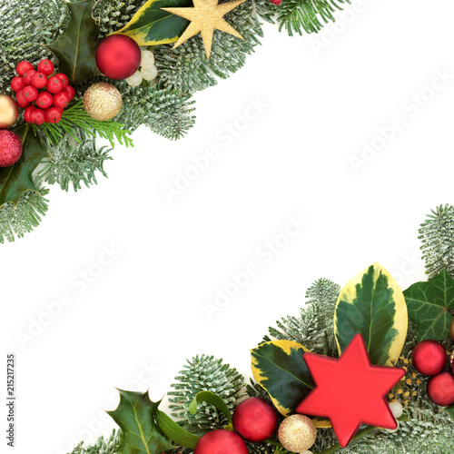 Foto Murales Christmas background border with red and gold star and ball bauble decorations, holly, fir, mistletoe and ivy isolated on white background.  Festive theme.