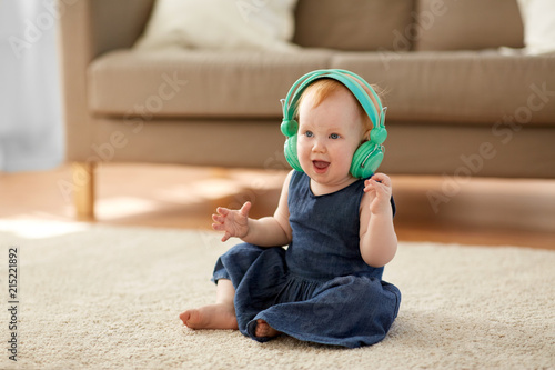 Foto Spatwand Muziek childhood, kids and technology concept - lovely redhead baby girl in headphones listening to music at home