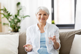 age, medicine, healthcare and people concept - senior woman with pills and glass of water at home