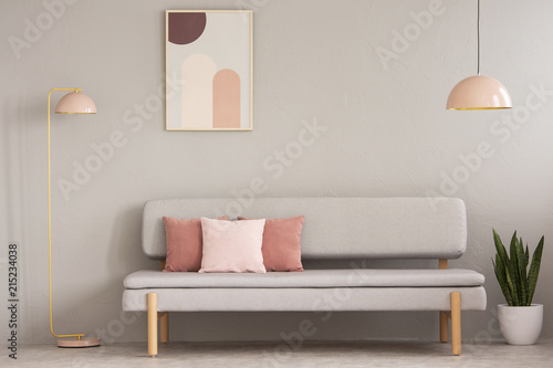 Leinwandbild Motiv Real photo of grey sitting room interior with couch with cushions, pastel pink lamps, fresh plant and simple poster on the wall