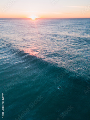 In de dag Zonsopgang Aerial view of surfers waiting for wave during sunrise.