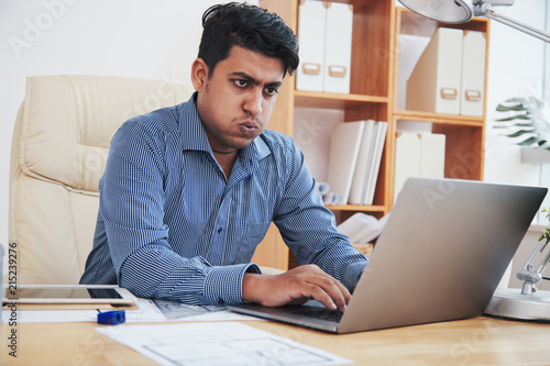 Foto Murales Tired Indian businessman typing on laptop and working in office