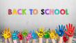 """Leinwandbild Motiv angemalte Kinderhände und die Nachricht """"Back to school"""" in bunten Farben"""