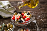 pouring virgin olive oil on vegetarian salad with fresh vegetables, feta and green olives. - 215256426