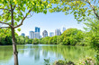 Cityscape, skyline view in Piedmont Park in Atlanta, Georgia looking, framing through trees, scenic water, urban city skyscrapers downtown at Lake Clara Meer