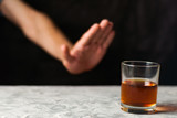 Man hand showing denial and transparent glass with alcohol on gray cement on black background - 215270418