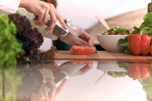 Close Up of human hands cooking vegetable salad in kitchen on the glass table with reflection. Healthy meal, and vegetarian food concept - 215297200