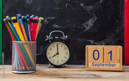 Wrzesień 1 data, budzik i kolorowe kredki na tablica tło