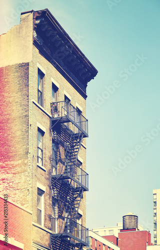 Retro toned picture of an od building with fire escape ladders, New York City, USA. - 215334433