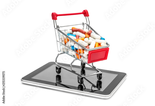 Foto Spatwand Apotheek Full shopping cart of pills with tablet PC on white.