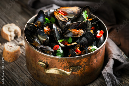 Fototapeta Mussels with coriander and chili peppers on wooden table