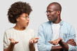 Confused African American couple look at each other angrily, clasp hands, don`t know where their money disappeared, wear round spectacles, isolated over white background. Family has problems