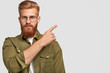 Leinwandbild Motiv Attractive bearded male with thick ginger beard and hair, appealing look, points at upper right corner, shows blank space for your advertising content, isolated over white background. Look there!