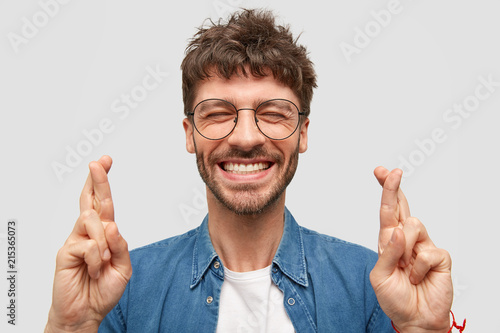 Leinwandbild Motiv Happy unshaven male with broad smile, shows white teeth, crosses fingers for good luck, being in high spirit stands over white background wears fashionable denim shirt. Positive guy makes hope gesture