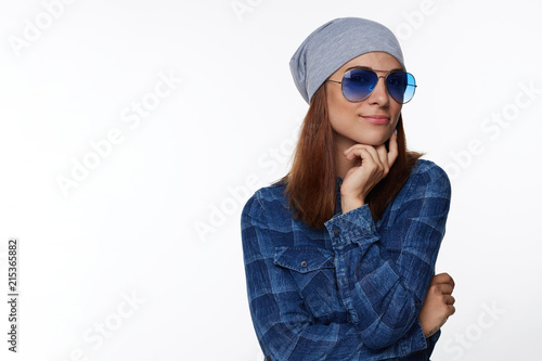 Telling joke to friend. Positive young good-looking European female student in hat and glasses, crossing hands together over chest and smiling joyfully, being in good mood while trying help customer.
