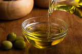 Extra virgin olive oil flowing from it's bottle - 215368283