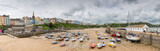 Tenby fishing port harbour at low tide, captured in a panoramic view