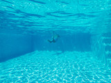 underwater image of an outside villa swimming pool with some steps at one side. A senior man is swimming at one end. The water is clear blue and the sunlight is making patterns