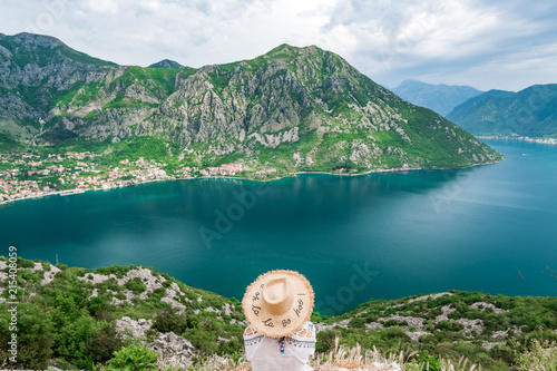 Foto Spatwand Groen blauw Concept picture of traveling, woman with hat looking at view of famous Gospa-od-Shkrpjela from a bird's-eye view of the Boko-Kotor Bay in Montenegro