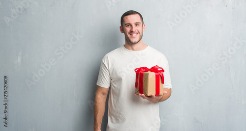 Foto Murales Young caucasian man over grey grunge wall holding a present with a happy face standing and smiling with a confident smile showing teeth