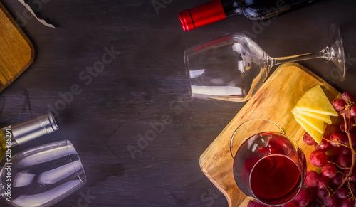 Bottle of red wine and two wine glasses on table with grape friut, copy space on dark table, toned image, banner