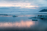 Dusk picture of Glacier Lagoon in Iceland with low altitude clouds and glacier moraine in the background - 215435893