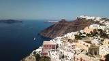 Aerial drone view over the majestic cliffs on the coast of Santorini, Greece including houses on the hill and a speedboat in the Aegean Sea - 215443601