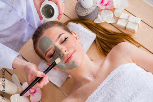 Leinwandbild Motiv Young woman in spa health concept with face mask