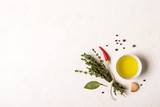 Olive oil and bouquet of thyme on a white stone background - 215477618