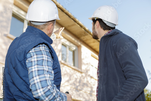 Plakat architect and mason inspecting the exterior of the house